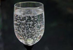 透明のグラスに透明の炭酸水が入っている